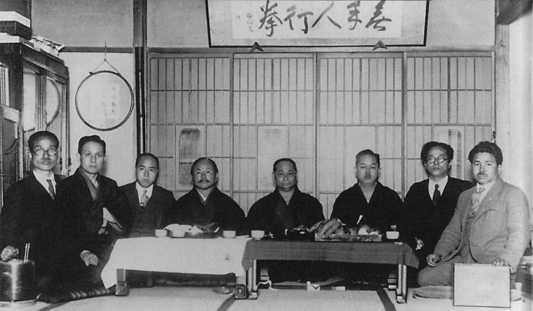 Karate masters sitting around a table during a meeting.
